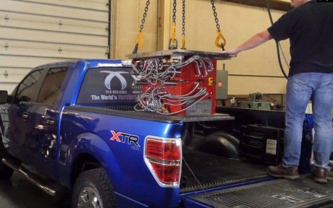 Plastic injection mold being loaded into the back of an XMD-branded Ford Pickup truck